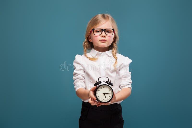 Το λατρευτό χαριτωμένο μικρό κορίτσι στο άσπρο πουκάμισο, τα γυαλιά και το μαύρο παντελόνι κρατούν το ξυπνητήρι στοκ εικόνες
