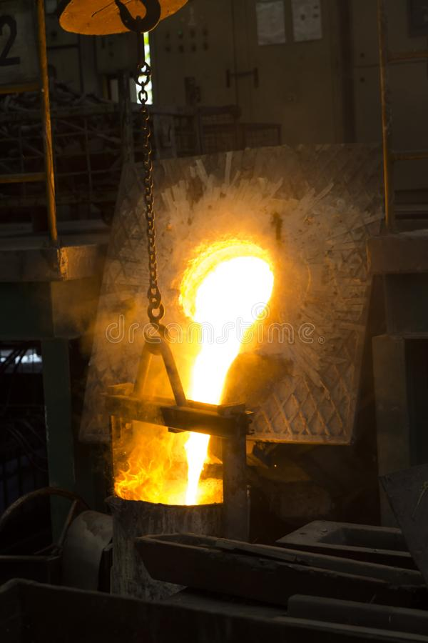 Το λειωμένο λειωμένο μέταλλο σιδήρου έχυσε μέσα στην κουτάλα στοκ εικόνα