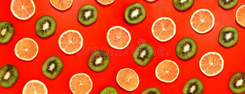 Το λεμόνι και kiwifruit οι φέτες στις γραμμές με τις σκληρές σκιές στο κόκκινο υπόβαθρο, επίπεδο βάζουν την εικόνα στοκ φωτογραφία με δικαίωμα ελεύθερης χρήσης