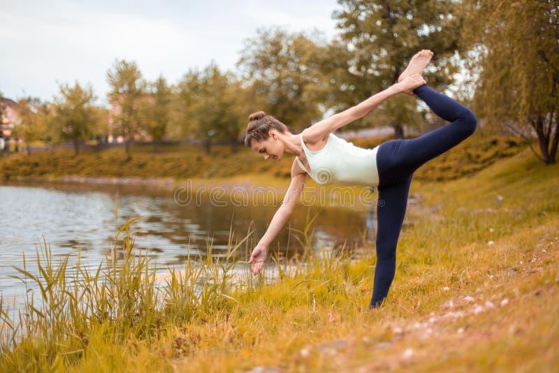 Το λεπτό κορίτσι brunette πηγαίνει μέσα για τον αθλητισμό και εκτελεί τη γιόγκα θέτει το φθινόπωρο στη φύση από τη λίμνη στοκ εικόνες με δικαίωμα ελεύθερης χρήσης