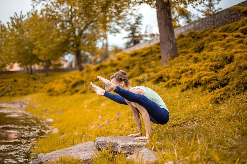 Το λεπτό κορίτσι brunette πηγαίνει μέσα για τον αθλητισμό και εκτελεί τη γιόγκα θέτει το φθινόπωρο στη φύση από τη λίμνη στοκ εικόνα με δικαίωμα ελεύθερης χρήσης