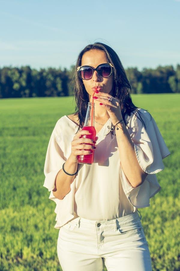 Το λεπτό κορίτσι Youn με τα ποτήρια και η σγουρή τρίχα χαμογελούν και πίνουν ένα οινοπνευματώδες ή μη οινοπνευματούχο κόκκινο κοκ στοκ φωτογραφίες με δικαίωμα ελεύθερης χρήσης