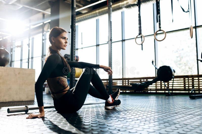 Το λεπτό σκοτεινός-μαλλιαρό κορίτσι που ντύνεται στα μαύρα αθλητικά ενδύματα κάθεται στο πάτωμα και κάνει το τέντωμα στη γυμναστι στοκ φωτογραφία