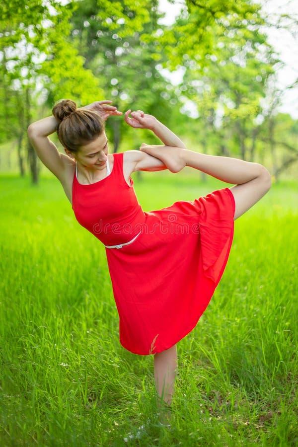 Το λεπτό όμορφο κορίτσι brunette σε ένα κόκκινο φόρεμα εκτελεί τη γιόγκα θέτει σε ένα θερινό πάρκο Πράσινο δάσος στο ηλιοβασίλεμα στοκ φωτογραφίες με δικαίωμα ελεύθερης χρήσης