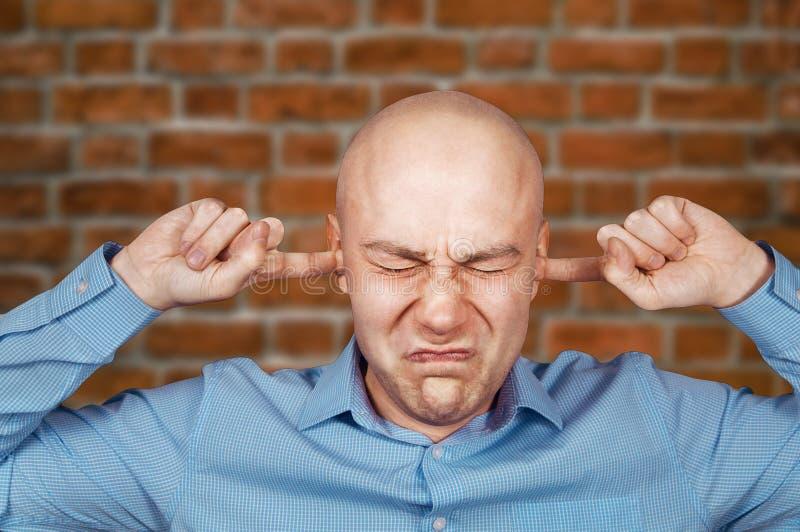 Το λευκό φαλακρό άτομο πορτρέτου κλείνει τα αυτιά στο μπλε πουκάμισο στο υπόβαθρο τουβλότοιχος στοκ εικόνα