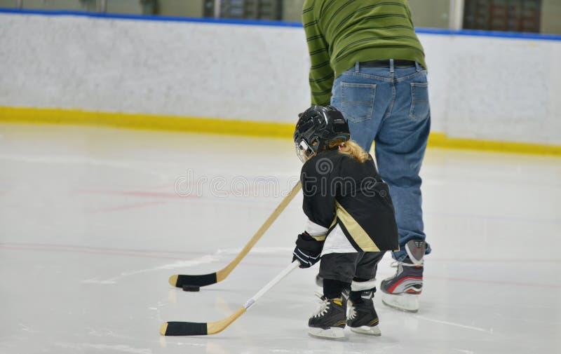 Το λεωφορείο χόκεϋ διδάσκει έναν λίγο παίκτη κοριτσιών χόκεϋ για να παίξει το χόκεϋ πάγου Η άποψη είναι από το πίσω μέρος τους στοκ εικόνες