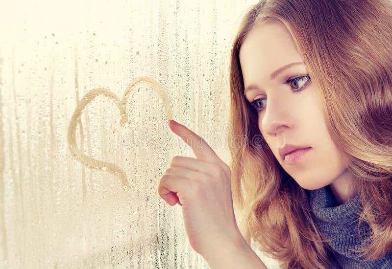 Το λυπημένο κορίτσι επισύρει την προσοχή μια καρδιά στο παράθυρο στη βροχή στοκ εικόνες με δικαίωμα ελεύθερης χρήσης