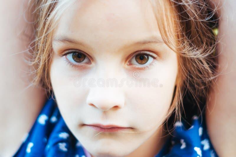 Το λυπημένο μικρό κορίτσι εξετάζει με το σοβαρό πρόσωπο τη κάμερα στοκ εικόνα