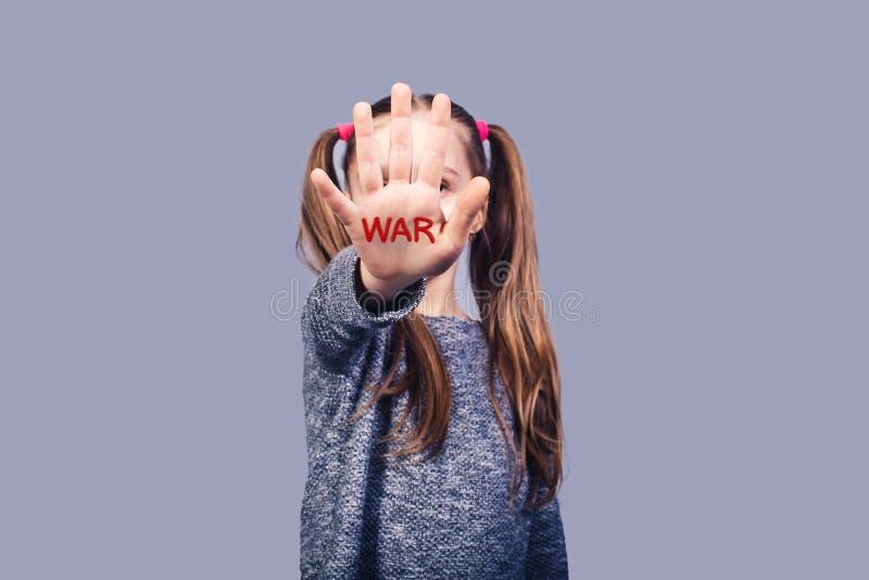 Το λυπημένο μικρό κορίτσι παρουσιάζει σημάδι στάσεων χεριών Κλήσεις παιδιών έννοιας για να τελειώσει τον πόλεμο στοκ φωτογραφία