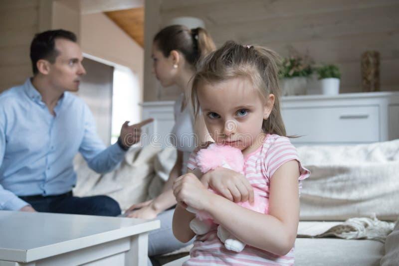 Το λυπημένο μικρό κορίτσι φόβισε όταν έχουν οι γονείς την πάλη στο σπί στοκ φωτογραφίες με δικαίωμα ελεύθερης χρήσης