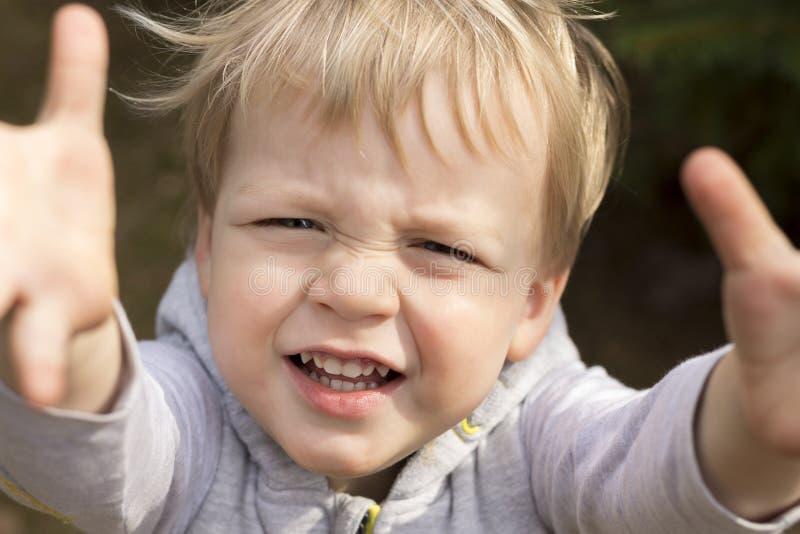 Το λυπημένο φωνάζοντας μικρό παιδί τραβά τα χέρια του επάνω Κλείστε επάνω το πορτρέτο του αγοράκι που ζητά τις συλλογές στοκ εικόνες με δικαίωμα ελεύθερης χρήσης