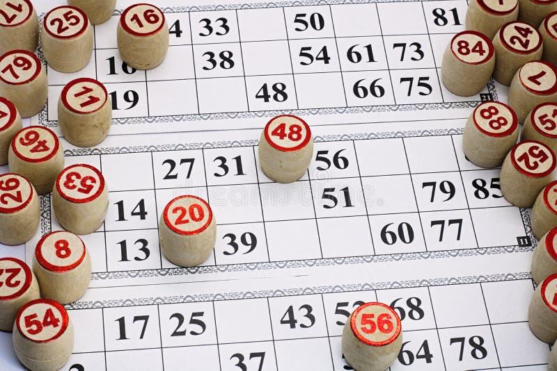 Το λότο επιτραπέζιων παιχνιδιών, κάρτες με τους αριθμούς για το παιχνίδι, βυτία είναι στις κάρτες κατά τη διάρκεια του παιχνιδιού στοκ φωτογραφία
