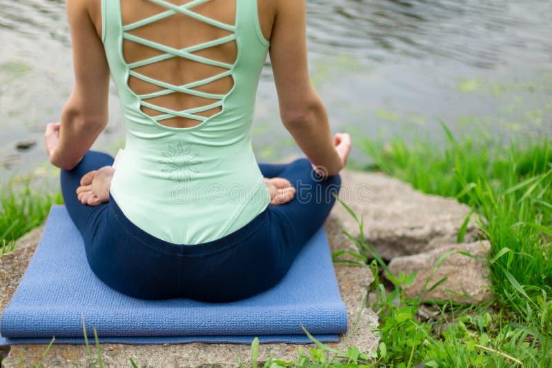 Το μάθημα γιόγκας άσκησης γυναικών γιόγκας, αναπνοή, περισυλλογή, που κάνει την άσκηση Ardha Padmasana, μισός λωτός θέτει με τη χ στοκ φωτογραφίες με δικαίωμα ελεύθερης χρήσης