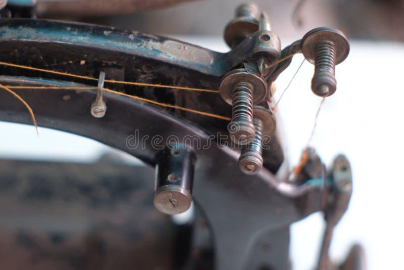 Το μέρος κινηματογραφήσεων σε πρώτο πλάνο μιας παλαιάς ράβοντας μηχανής και η λεπτομέρεια ρυθμίζουν επάνω το νήμα στοκ φωτογραφία
