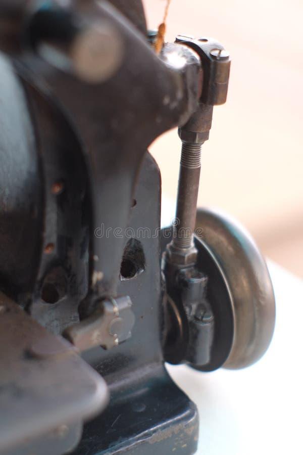 Το μέρος κινηματογραφήσεων σε πρώτο πλάνο μιας παλαιάς ράβοντας μηχανής και η λεπτομέρεια ρυθμίζουν επάνω το νήμα στοκ εικόνες
