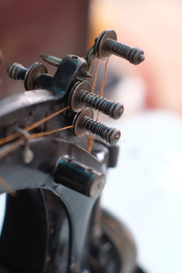 Το μέρος κινηματογραφήσεων σε πρώτο πλάνο μιας παλαιάς ράβοντας μηχανής και η λεπτομέρεια ρυθμίζουν επάνω το νήμα στοκ φωτογραφία με δικαίωμα ελεύθερης χρήσης