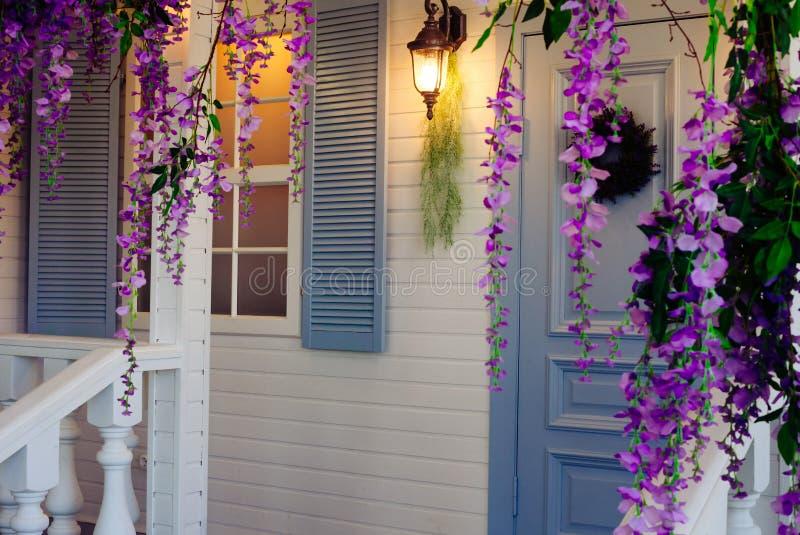 Το μέρος σπιτιών με ένα φανάρι, μια μπλε πόρτα και ένα παράθυρο και ένα wisteria ανθίζει τη διακόσμηση στοκ εικόνα με δικαίωμα ελεύθερης χρήσης