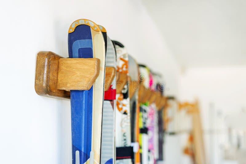 Το μέρος του σκι που κρεμιέται στον προσαρμοσμένο ξύλινο τοίχο τοποθετεί στο γκαράζ για την εποχιακή αποθήκευση Ακραίος εξοπλισμό στοκ φωτογραφίες