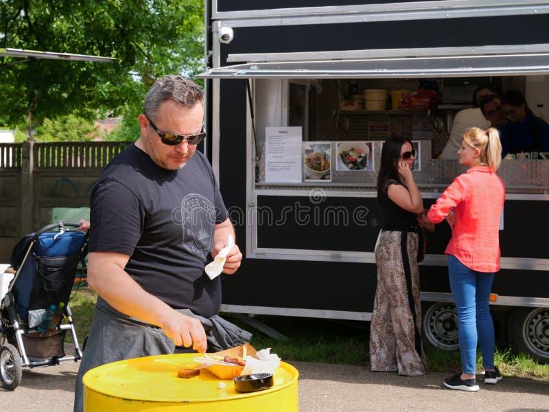 Το μέσο ηλικίας άτομο τρώει τα τρόφιμα οδών σε έναν πίνακα τυμπάνων στοκ φωτογραφία με δικαίωμα ελεύθερης χρήσης