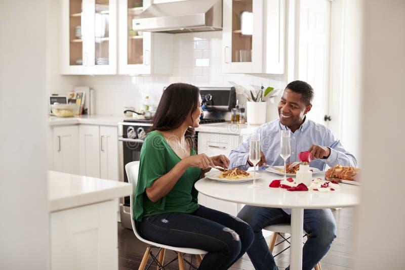 Το μέσο ηλικίας ζεύγος αφροαμερικάνων που τρώει ένα ρομαντικό γεύμα μαζί στην κουζίνα τους, κλείνει επάνω στοκ φωτογραφία
