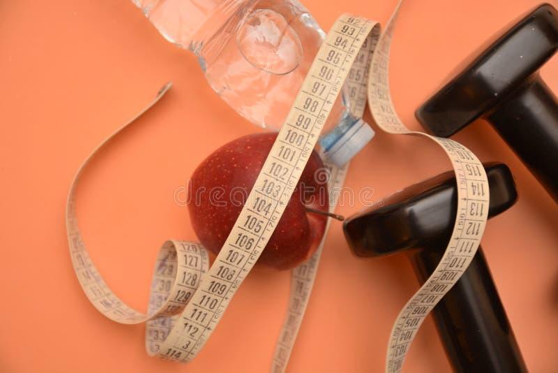 Το μήλο υγείας νερού Dumbells measur μετρά την ικανότητα διατροφής και το wellness ομορφιάς ενεργειακού αθλητισμού τροφίμων ρεικι στοκ εικόνες