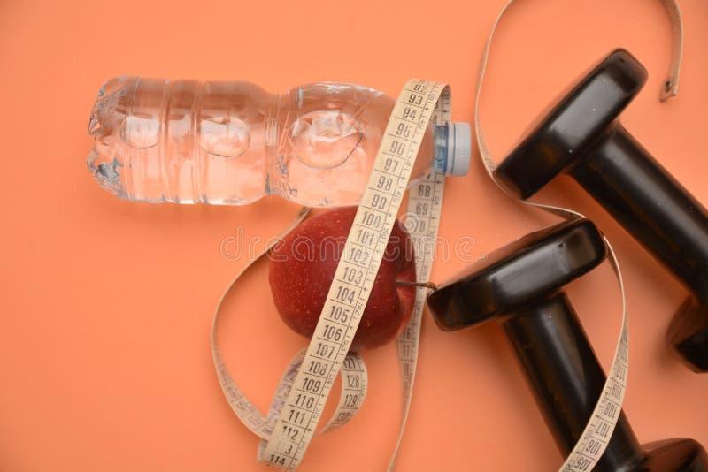 Το μήλο υγείας νερού Dumbells measur μετρά την ικανότητα διατροφής και το wellness ομορφιάς ενεργειακού αθλητισμού τροφίμων ρεικι στοκ εικόνα με δικαίωμα ελεύθερης χρήσης