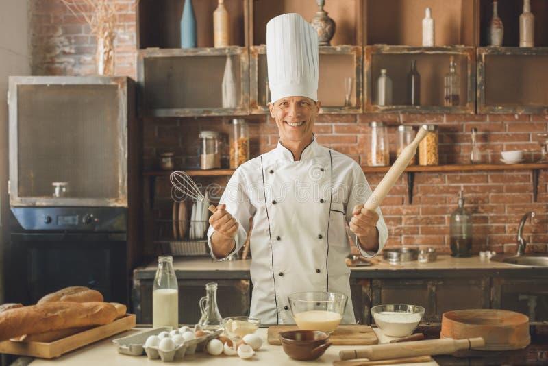 Το μαγείρεμα αρχιμαγείρων αρτοποιείων ψήνει στην κουζίνα στοκ εικόνες