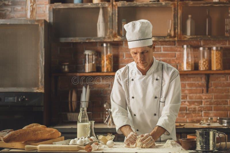 Το μαγείρεμα αρχιμαγείρων αρτοποιείων ψήνει στον επαγγελματία κουζινών στοκ εικόνες