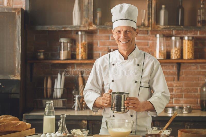 Το μαγείρεμα αρχιμαγείρων αρτοποιείων ψήνει στον επαγγελματία κουζινών στοκ φωτογραφία