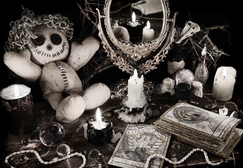 Το μαγικό τελετουργικό με την κούκλα βουντού, ο καθρέφτης και tarot οι κάρτες στον τρύγο grunge ορίζουν στοκ εικόνα