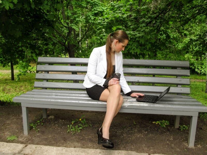 Το μακρυμάλλες κορίτσι σε ένα επιχειρησιακό κοστούμι κάθεται λοξά σε έναν πάγκο με τα πόδια της που διασχίζονται, κρατά τον καφέ  στοκ εικόνα