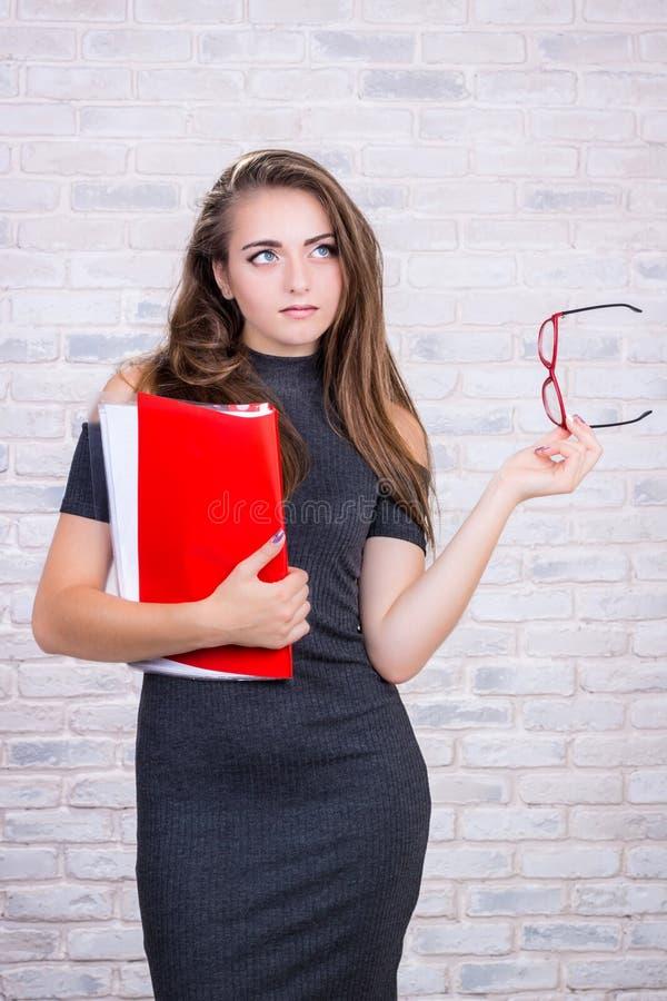 Το μακρυμάλλες κορίτσι μιμείται το διευθυντή γραφείων με τον κόκκινο φάκελλο στοκ φωτογραφία με δικαίωμα ελεύθερης χρήσης