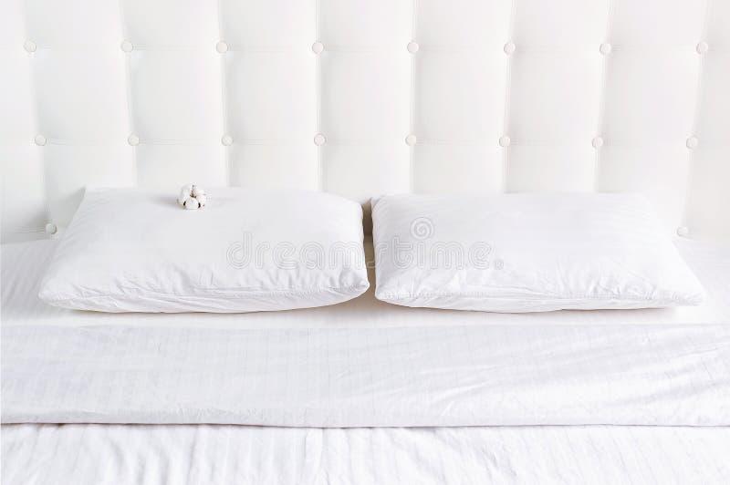Το μαλακό άσπρο γεμισμένο μαξιλάρι και το γενικό coverlet στο κρεβάτι στο υπόβαθρο του άσπρου δέρματος γέμισαν headboard Καθαρό μ στοκ εικόνα