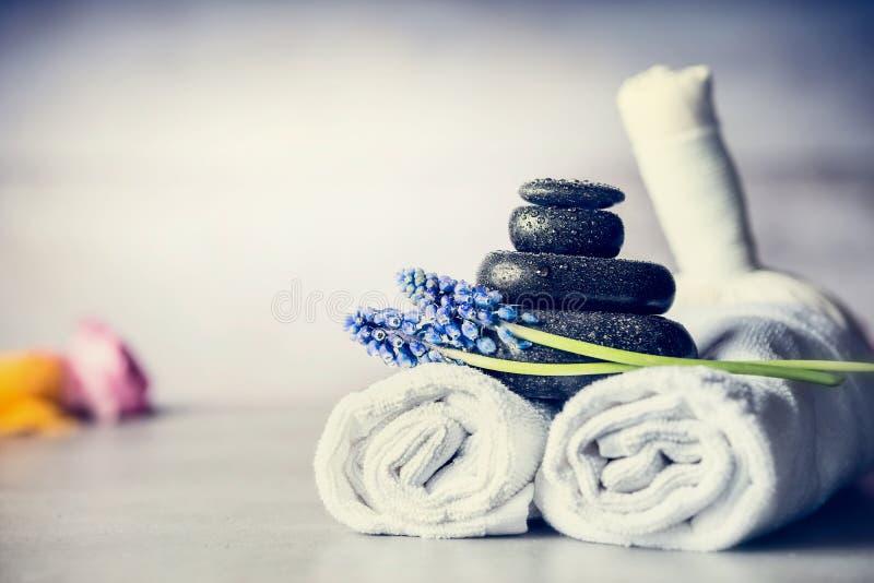Το μασάζ SPA που θέτει με τις πετσέτες, καυτές πέτρες και μπλε λουλούδια, κλείνει επάνω, έννοια wellness στοκ εικόνες