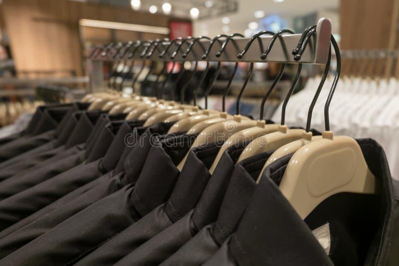 Το μαύρο και μπλε πουκάμισο κρεμά στο ράφι, πουκάμισα ατόμων ` s στις κρεμάστρες στην ντουλάπα στοκ εικόνες