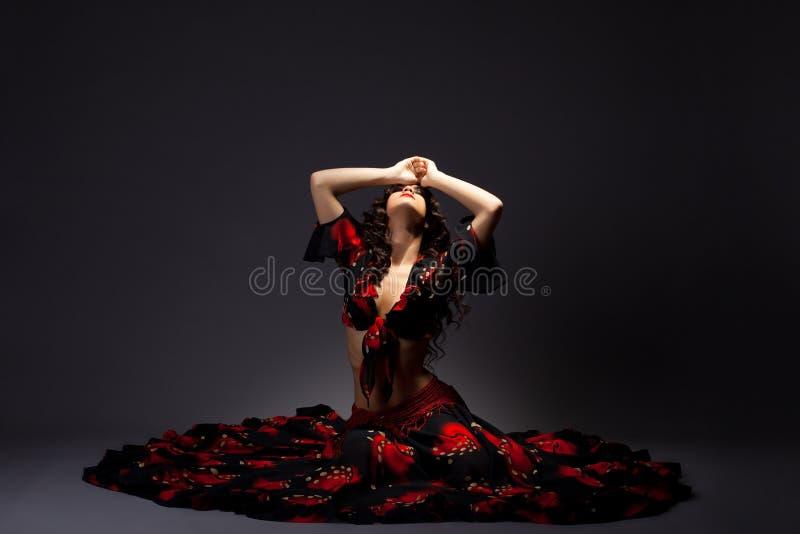 το μαύρο κόκκινο τσιγγάνων κοστουμιών κάθεται τις νεολαίες γυναικών στοκ εικόνα