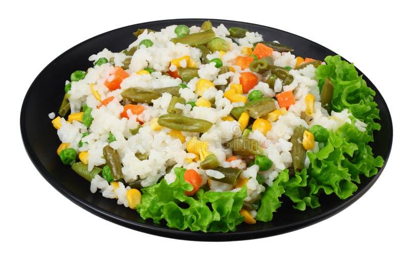 Το μαύρο πιάτο με το άσπρο ρύζι, πράσινα μπιζέλια, κονσερβοποίησε τους πυρήνες καλαμποκιού, πράσινα φασόλια περικοπών που απομονώ στοκ φωτογραφία