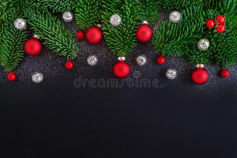 Το μαύρο υπόβαθρο Χριστουγέννων με τη διακόσμηση, τα κόκκινα berrys, το δέντρο μπιχλιμπιδιών και έλατου διακλαδίζονται στοκ φωτογραφία με δικαίωμα ελεύθερης χρήσης