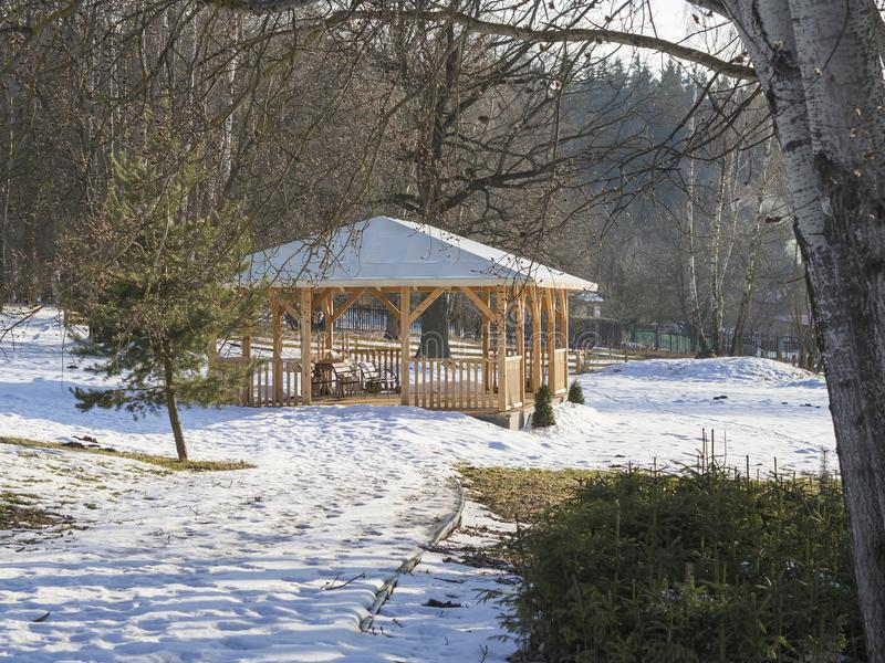 Το μεγάλο ξύλινο gazebo αλκοβών με τον πάγκο μέσα η σημύδα χιονιού στοκ εικόνα με δικαίωμα ελεύθερης χρήσης
