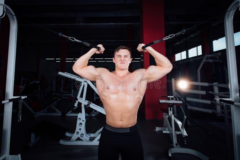 Το μεγάλο ισχυρό bodybuider χωρίς πουκάμισα καταδεικνύει τις ασκήσεις διασταυρώσεων Οι θωρακικοί μυ'ες και σκληρά κατάρτιση στοκ εικόνα