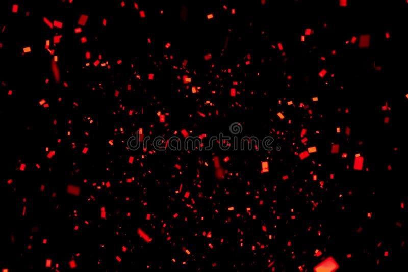 Το μειωμένο κόκκινο σπινθήρισμα Χριστουγέννων ακτινοβολεί κομφετί φύλλων αλουμινίου, στο μαύρο υπόβαθρο, τις διακοπές καλής χρονι στοκ εικόνα με δικαίωμα ελεύθερης χρήσης