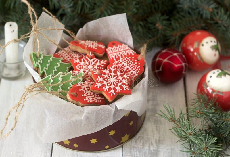 Το μελόψωμο σε ένα κιβώτιο κασσίτερου στο υπόβαθρο με τα παιχνίδια Χριστουγέννων, ένα κερί και ένα έλατο διακλαδίζεται στοκ εικόνα με δικαίωμα ελεύθερης χρήσης