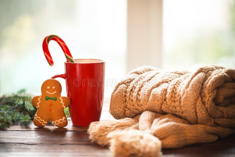 Το μελόψωμο Χριστουγέννων, η καραμέλα, ο καφές στο κόκκινο φλυτζάνι, το πλεκτό μαντίλι, οι κώνοι και οι κλάδοι χριστουγεννιάτικων στοκ φωτογραφία με δικαίωμα ελεύθερης χρήσης