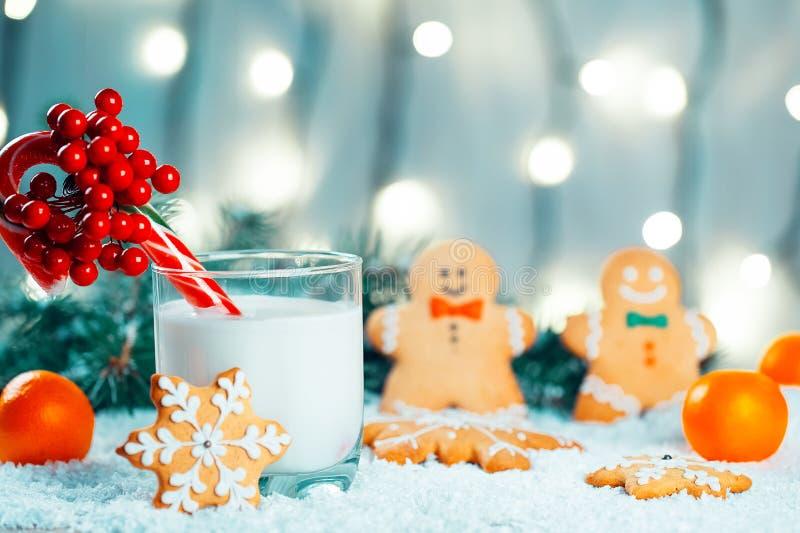 Το μελόψωμο Χριστουγέννων και το γάλα με τις διακοσμήσεις, χιόνι, κλάδοι χριστουγεννιάτικων δέντρων στο bokeh θόλωσαν το υπόβαθρο στοκ εικόνα