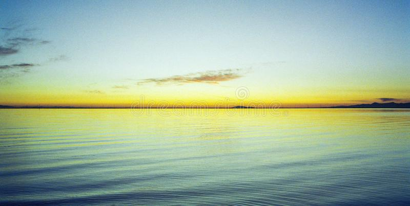 Το μεμονωμένα χρωματισμένο ηλιοβασίλεμα πετά το κίτρινο χρυσό χρώμα ο Ειρηνικός Ωκεανός στοκ φωτογραφίες με δικαίωμα ελεύθερης χρήσης