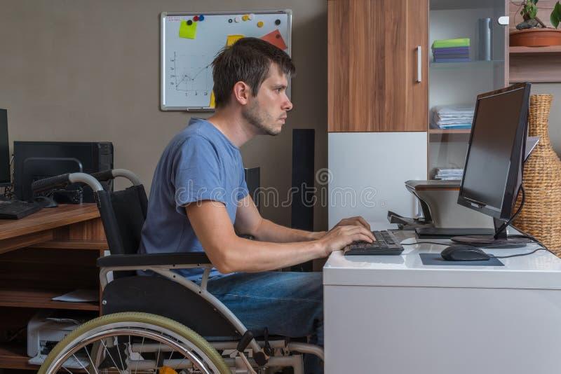 Το με ειδικές ανάγκες άτομο κάθεται στην αναπηρική καρέκλα και την εργασία στην αρχή στοκ εικόνες