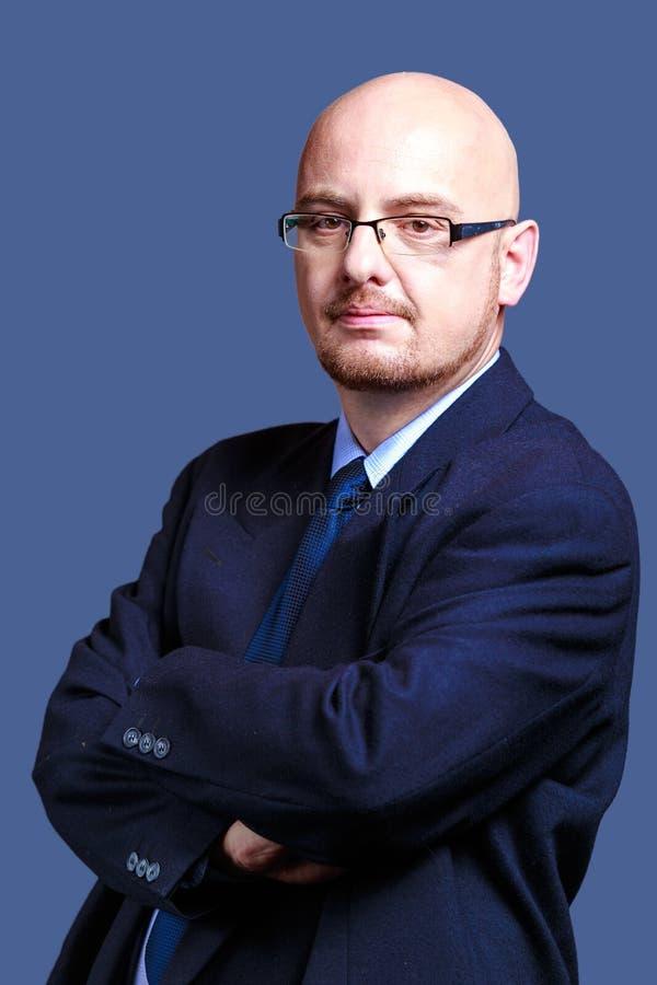 Τολμηρός διευθυνμένος τύπος με τα γυαλιά που εξετάζουν τη κάμερα που φορά jac στοκ εικόνα