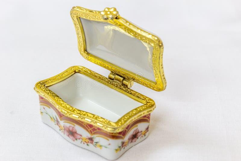 Το μικροσκοπικό ζωηρόχρωμο κιβώτιο κοσμημάτων με το χρυσό crimp σε ένα άσπρο υπόβαθρο Μακροεντολή με το εξαιρετικά ρηχό βάθος του στοκ εικόνα με δικαίωμα ελεύθερης χρήσης