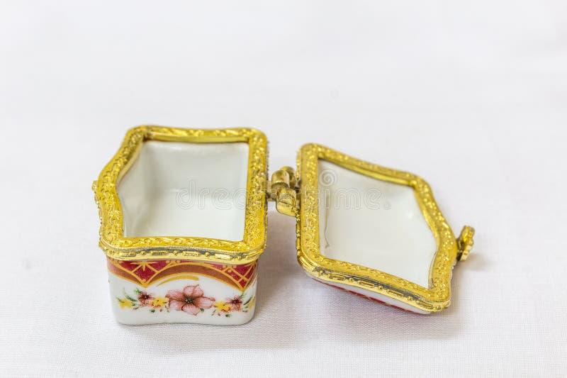 Το μικροσκοπικό ζωηρόχρωμο κιβώτιο κοσμημάτων με το χρυσό crimp σε ένα άσπρο υπόβαθρο Μακροεντολή με το εξαιρετικά ρηχό βάθος του στοκ εικόνες