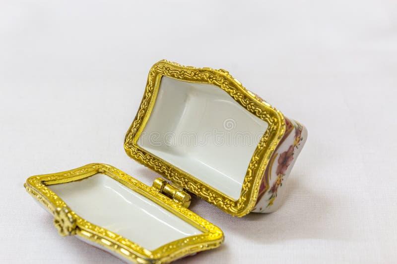 Το μικροσκοπικό ζωηρόχρωμο κιβώτιο κοσμημάτων με το χρυσό crimp σε ένα άσπρο υπόβαθρο Μακροεντολή με το εξαιρετικά ρηχό βάθος του στοκ φωτογραφίες